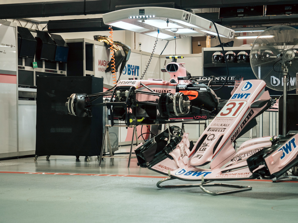 A disassembled race car in a racing garage.