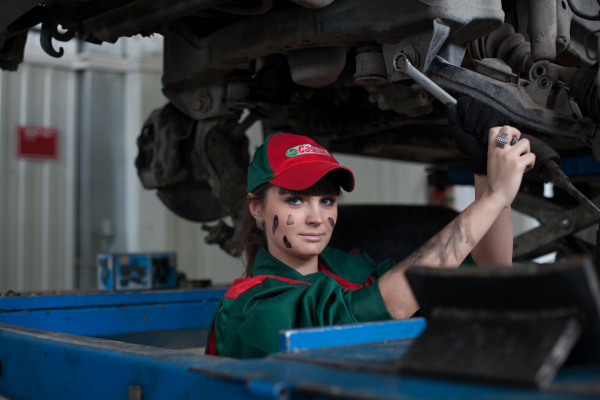 Woman working on a car in an auto dealership.