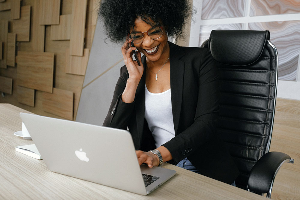 Young business woman smiling as she talks on her cell phone and works at her laptop.