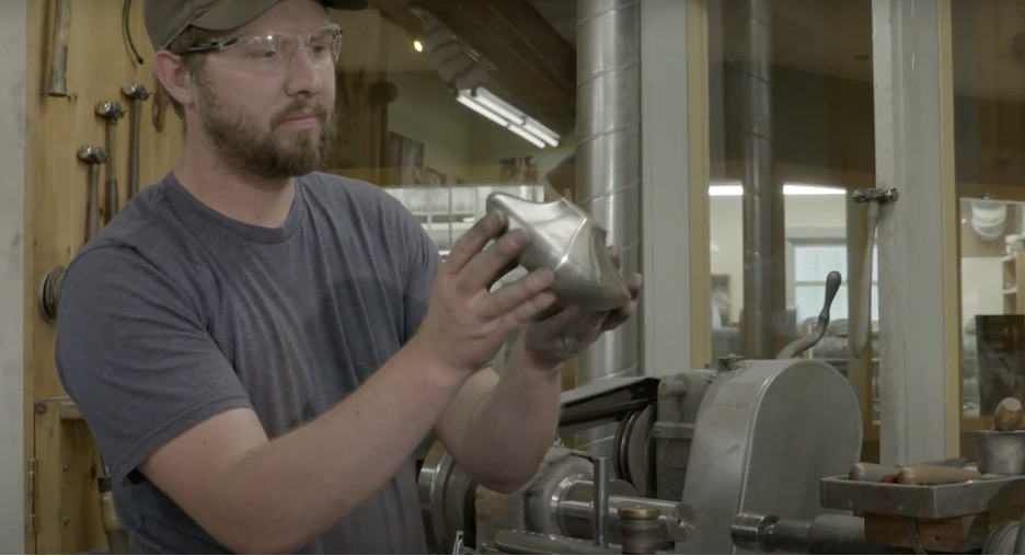 A man holding a part in a manufacturing facility.