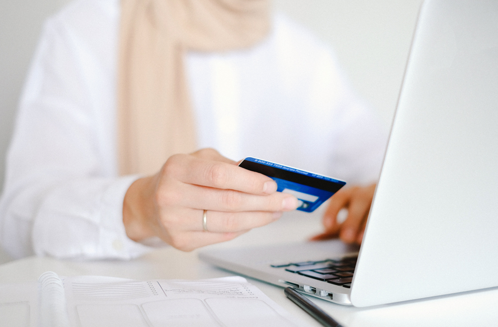 Woman holding credit card in while typing on laptop.
